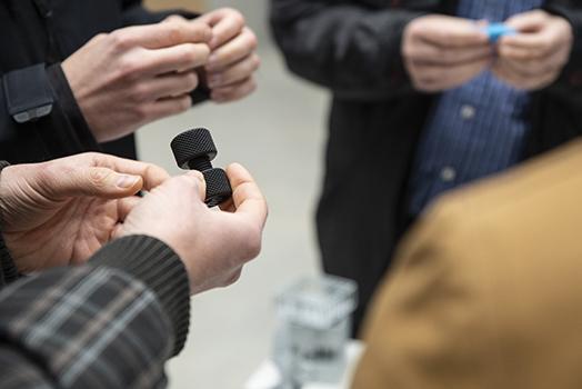 asistentes observando algunas de las piezas realizadas mediante impresión aditiva